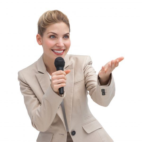A businesswoman with microphone showing something with her hand